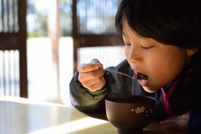 ぜんざいを食べる子ども